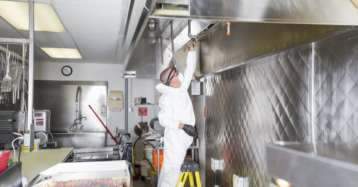a commercial cleaning employee cleans an industrial kitchen while wearing full protective gear.