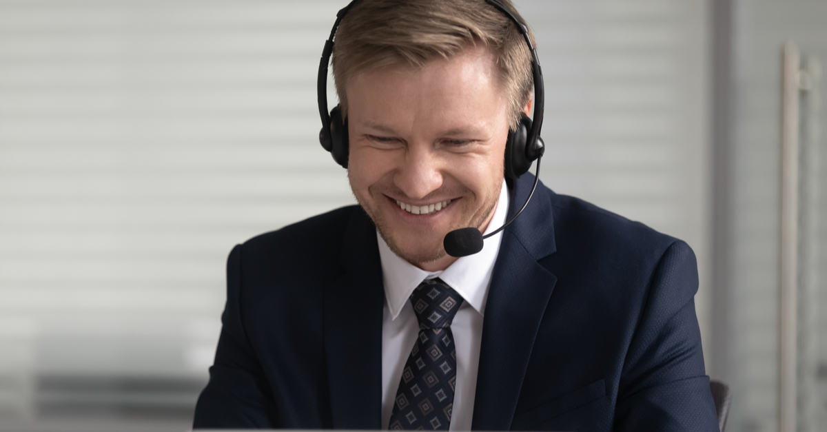 A man wears headphones with a microphone while looking at the computer.