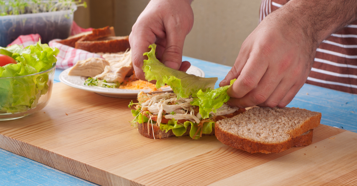hands are seen making a sandwich on a kitchen countertop at home.