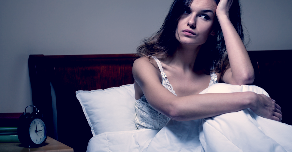 a woman sits up in bed because she's having trouble sleeping