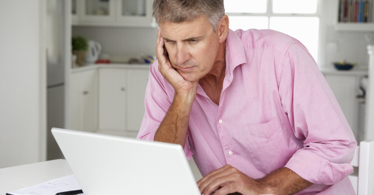 A man reviews his credit report on his computer with a serious expression on his face