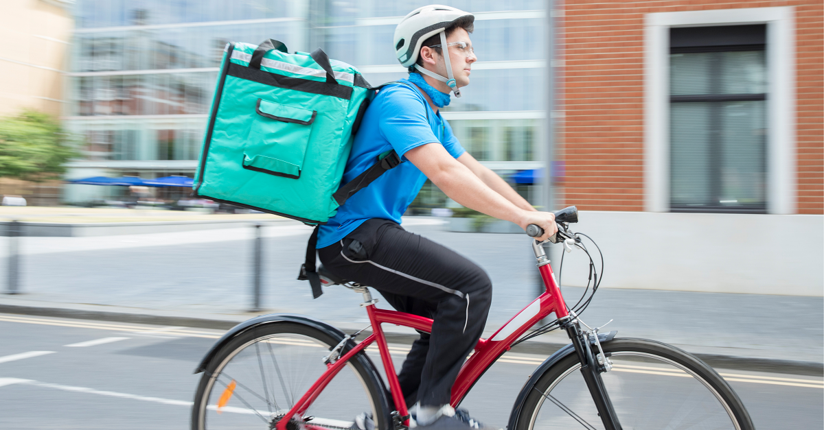 A gig worker rides a bike with a grocery delivery.