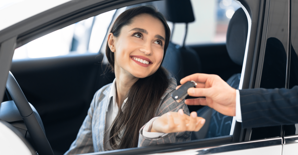 a woman sits in a car and accepts the keys to the car from the salesman