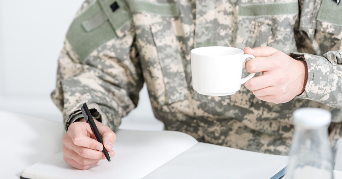 a military service member drinks coffee as he makes a checklist for his departure from service