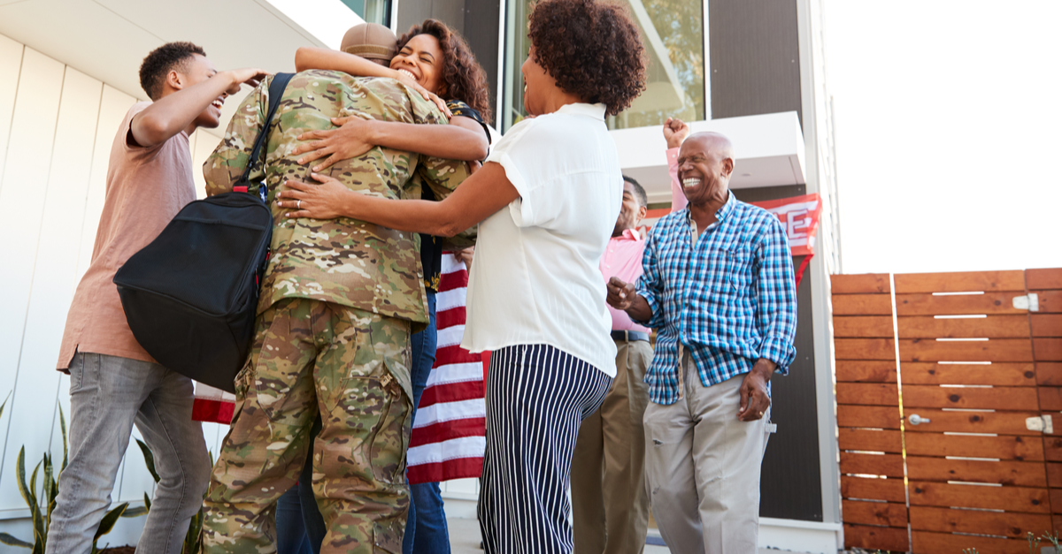 a military man is greeting by his family