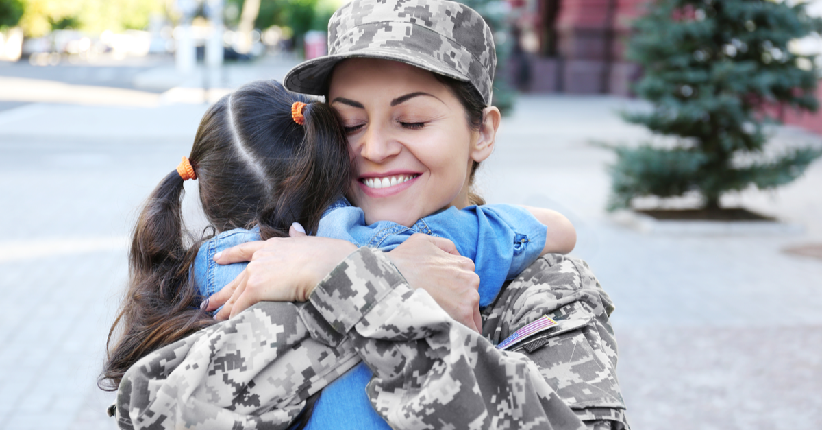 A military woman hugs her daughter