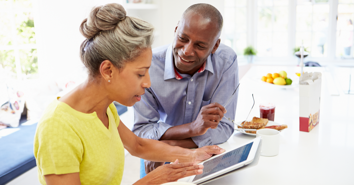 a mature couple looks at a computer tablet in the kitchen of their home