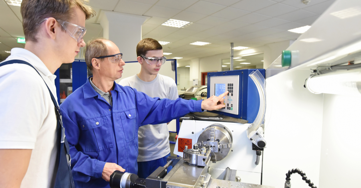 a professor at a technical college gives a mechanical lesson to two students wearing protective gear
