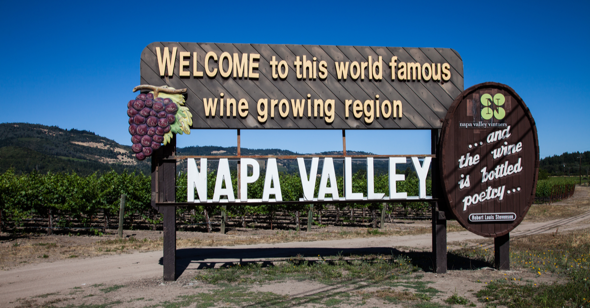 A wooden sign reads, 'Welcome to this world famous wine growing region Napa Valley,' in Napa Valley, California.