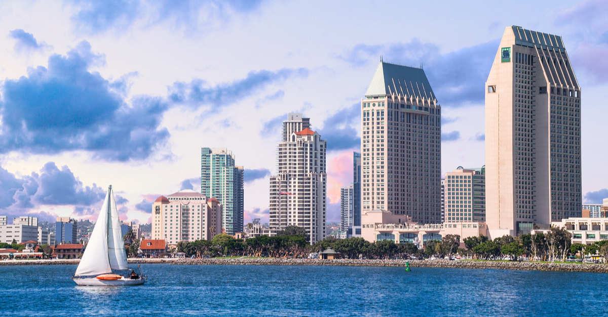 A sailboat is seen in the water with the San Diego downtown area in the background during the day.