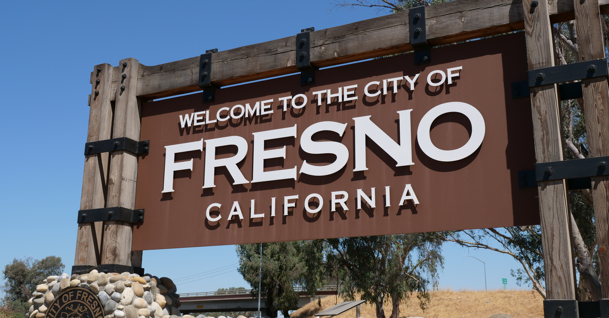 A wooden and stone sign reads 'Welcome to the City of Fresno, California.'