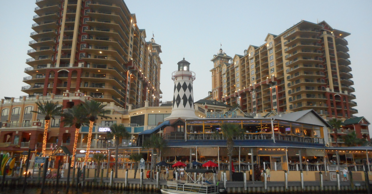 A large building and decorative lighthouse are shown in downtown Destin, Florida