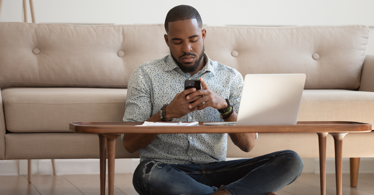 A man sits on the floor in front of his coffee table looking at his phone as he takes a break from freelance work.