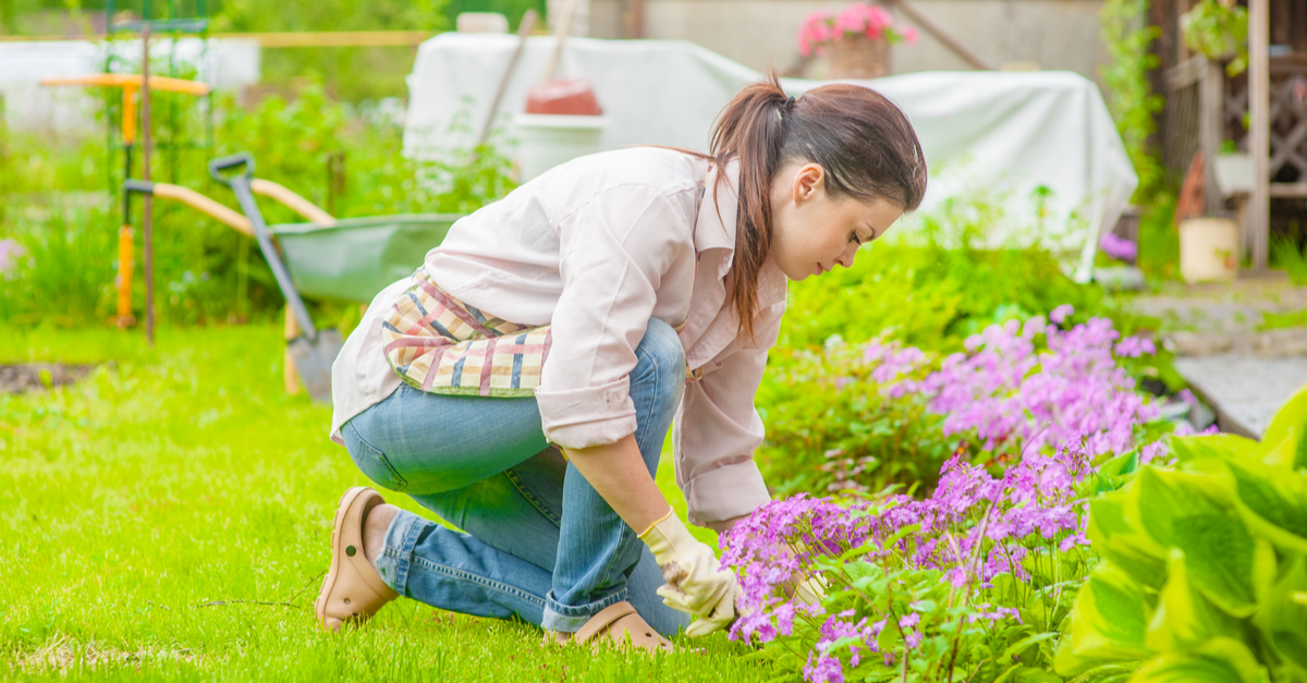 A woman tends to her garden in the backyard of the home she owns.