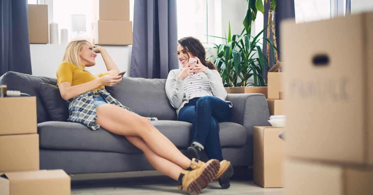 Two young woman, surrounded by moving boxes, sit on the couch in their new apartment