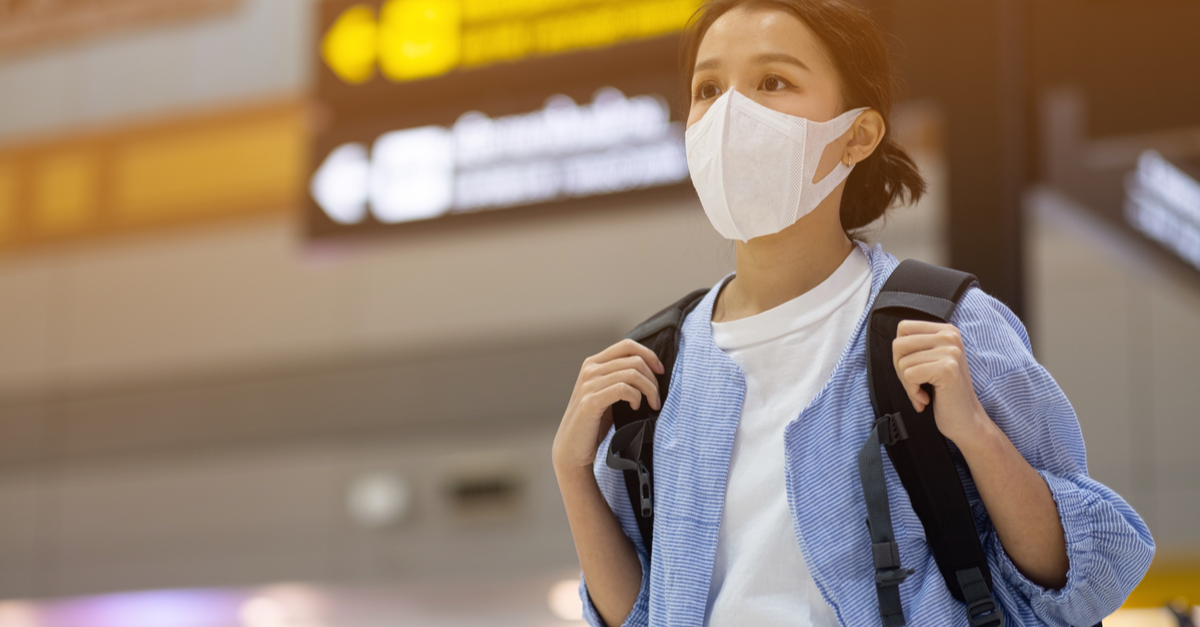 A young woman wearing a mask carries her backpack through the airport.