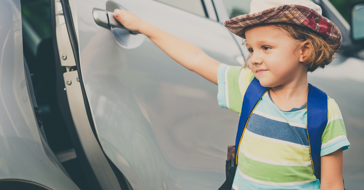 A young child opens the door to a car as he prepares to get inside