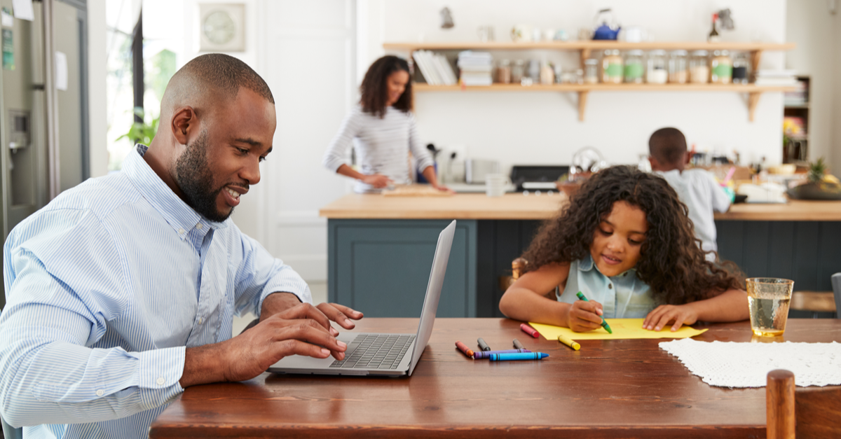 A man looks at life insurance options on his computer while his family engages in various activities nearby