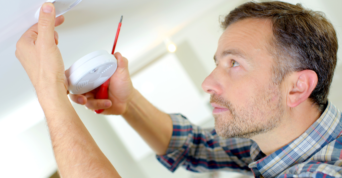 A man adds a smoke detector to his home