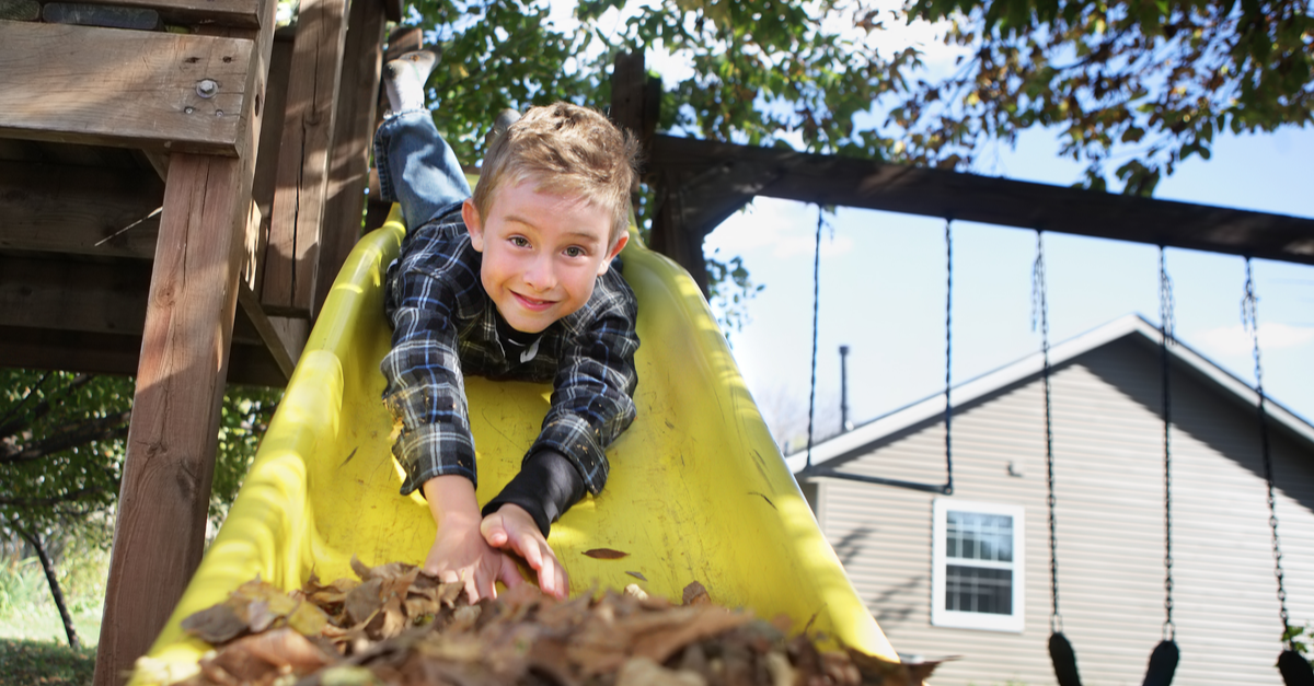 A little boy slides headfirst from his playset to a big pile of leaves