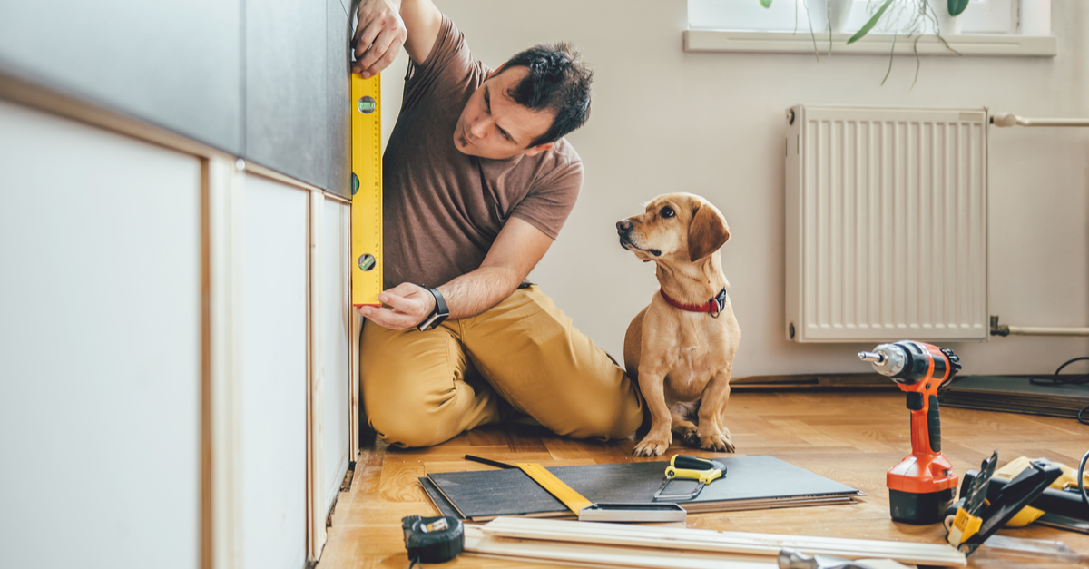 A man works on a home improvement project while his dog looks on