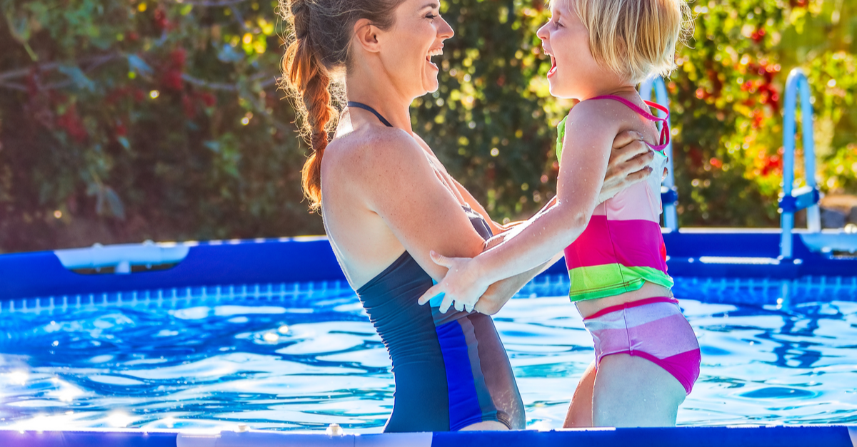 A mother and daughter enjoy playing in their backyard pool