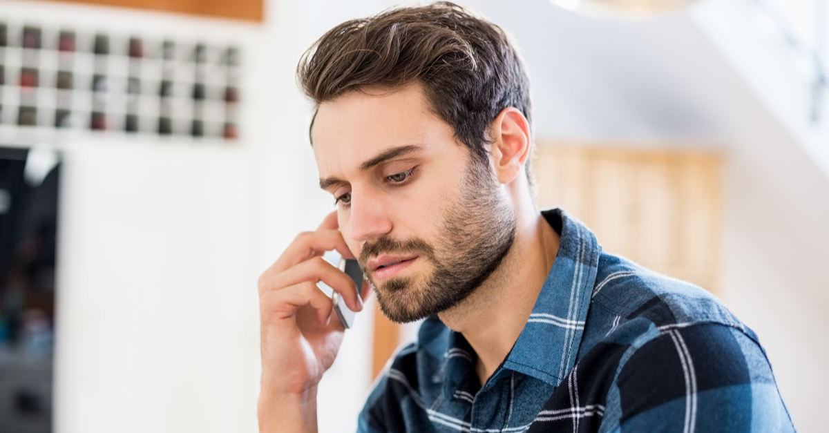 A man talks on the phone to his credit card company discussing his options for payment