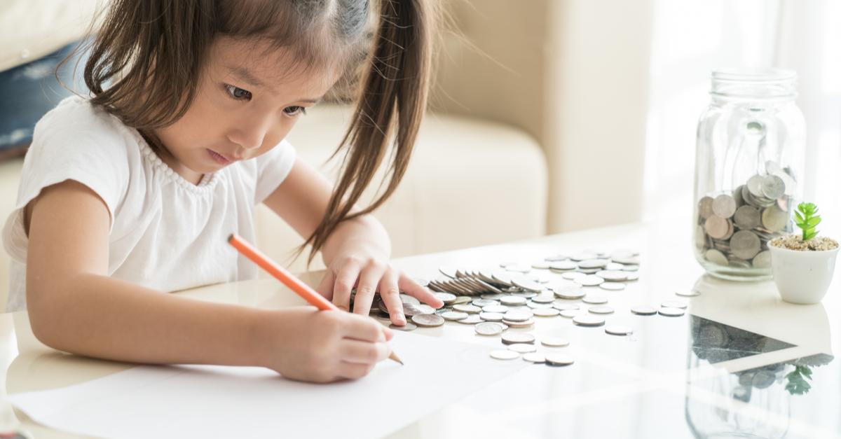 A little girl is seen counting money and writing things down