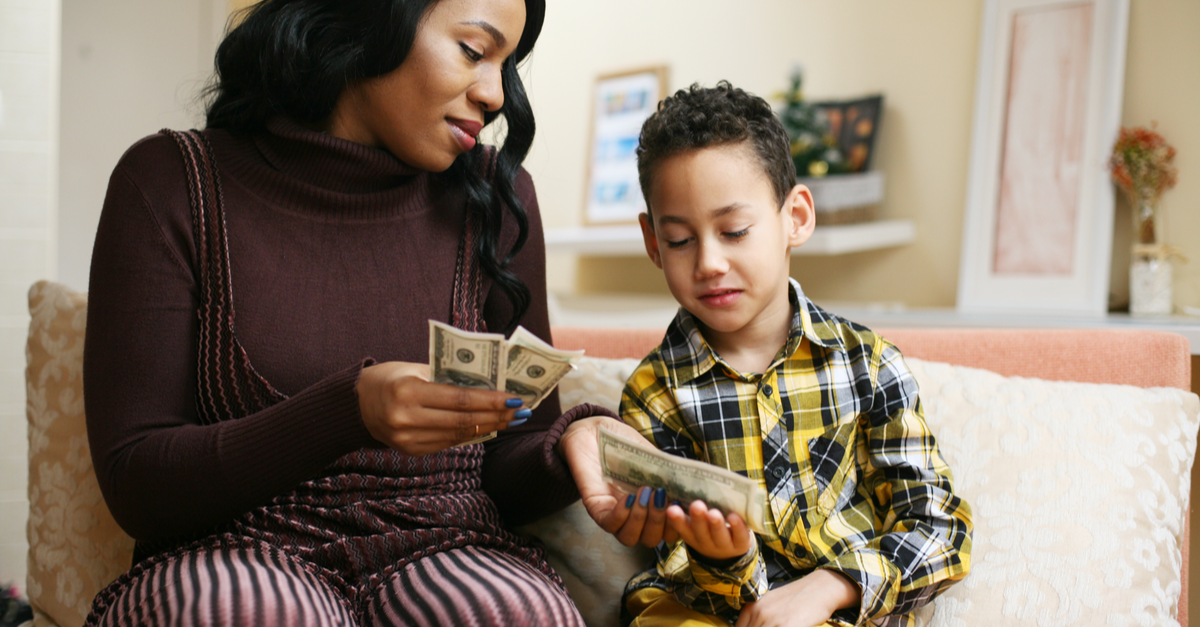 A boy and his mother discuss money and giving while holding money