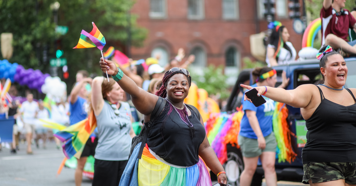 A woman enjoys walking in a parade during Pride Month