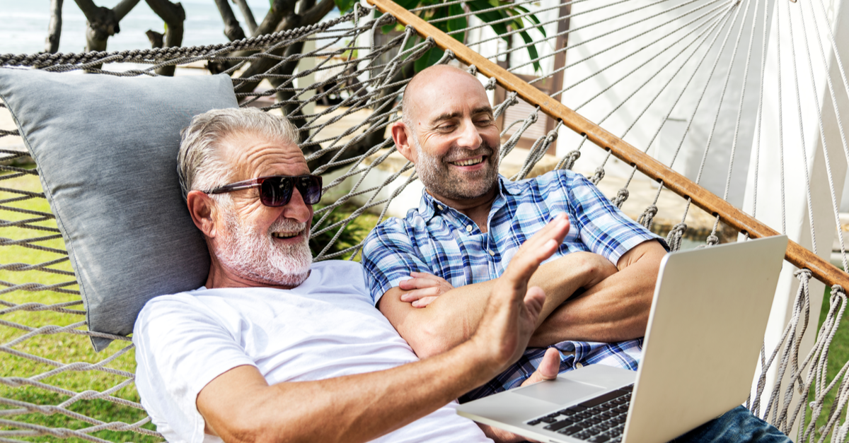 2 men enjoy looking at a computer while they sit in a hammock