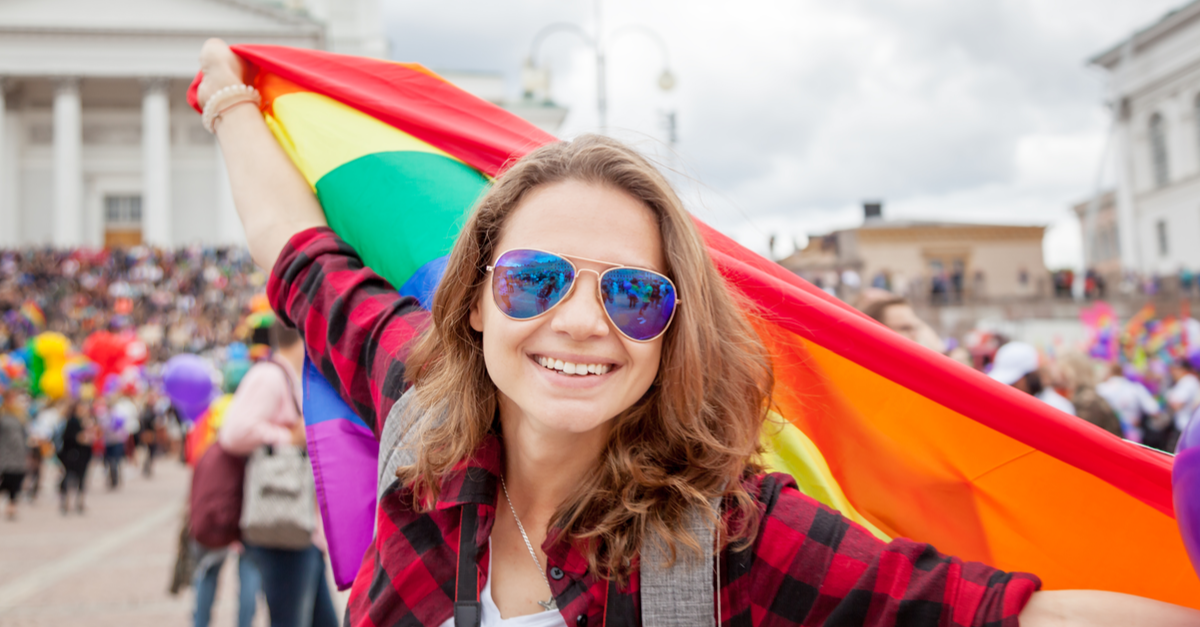 A woman waves a big flag during a pride celebration