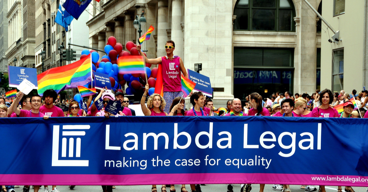 A group from Lamba Legal hold a sign during a pride parade in support of legal rights for LGBTQ+ people.