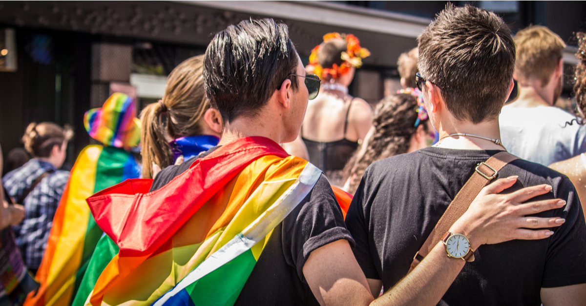 Two people are seen from behind with a rainbow flag as the watch a pride parade