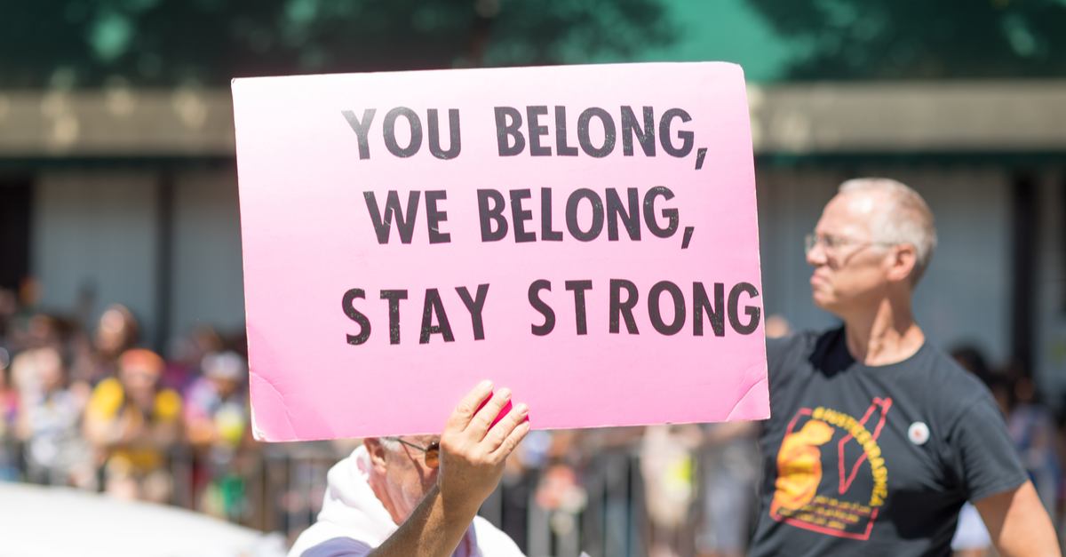 A man holds a sign that reads, 'You Belong, We Belong, Stay Strong.'