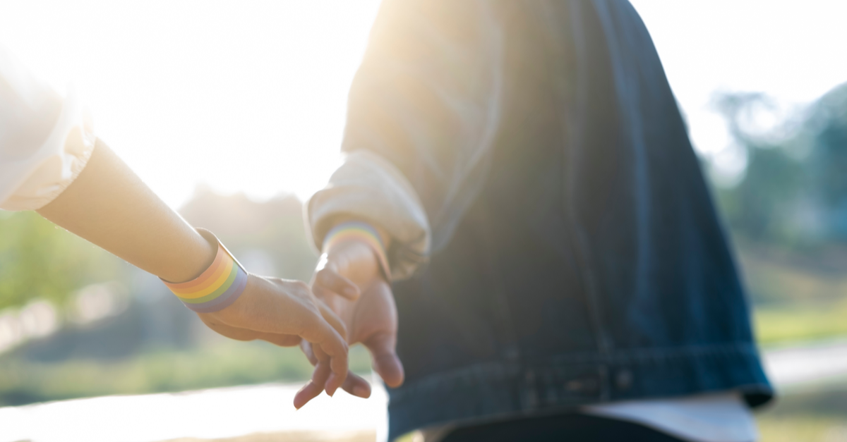 two people with rainbow bracelets hold hands