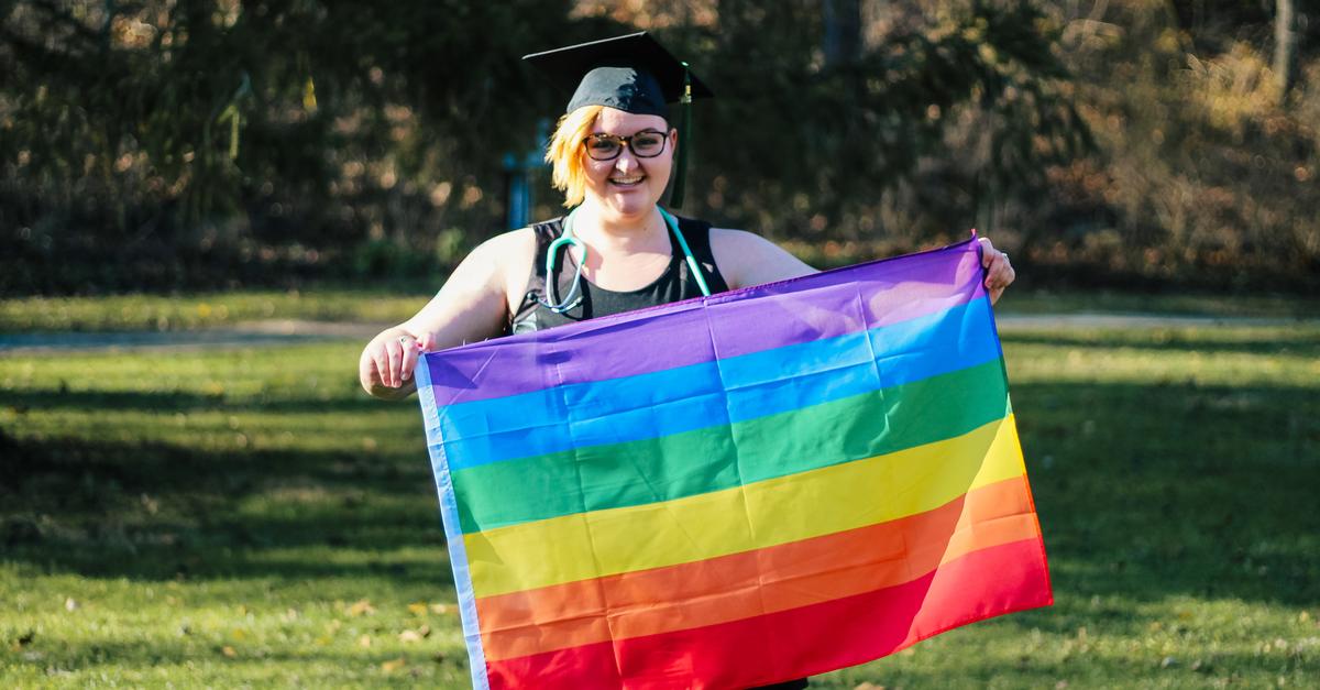 a woman holds an LGBTQ+ rainbow flag