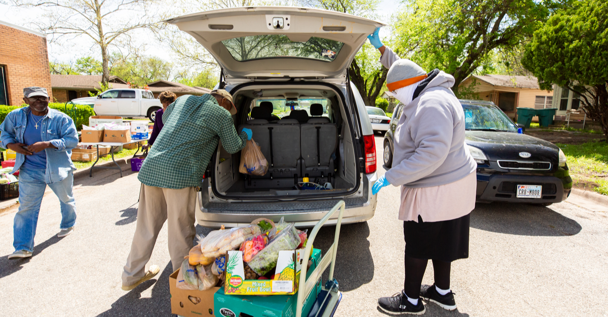 People load food into the back of a car at a food bank.