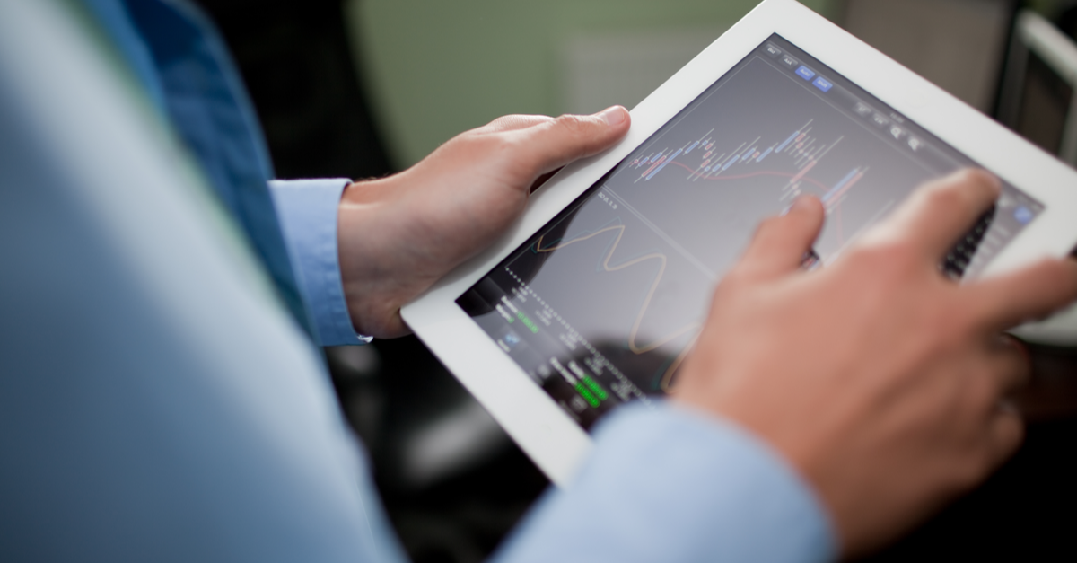 A businessman looks at the stock market on his tablet