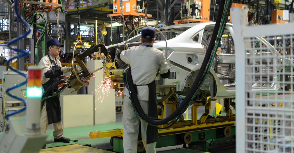 A man is working at an auto manufacturing plant