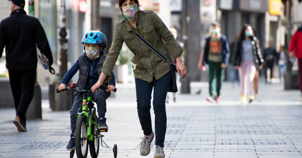A woman and boy on a bicycle are on the street with masks on.