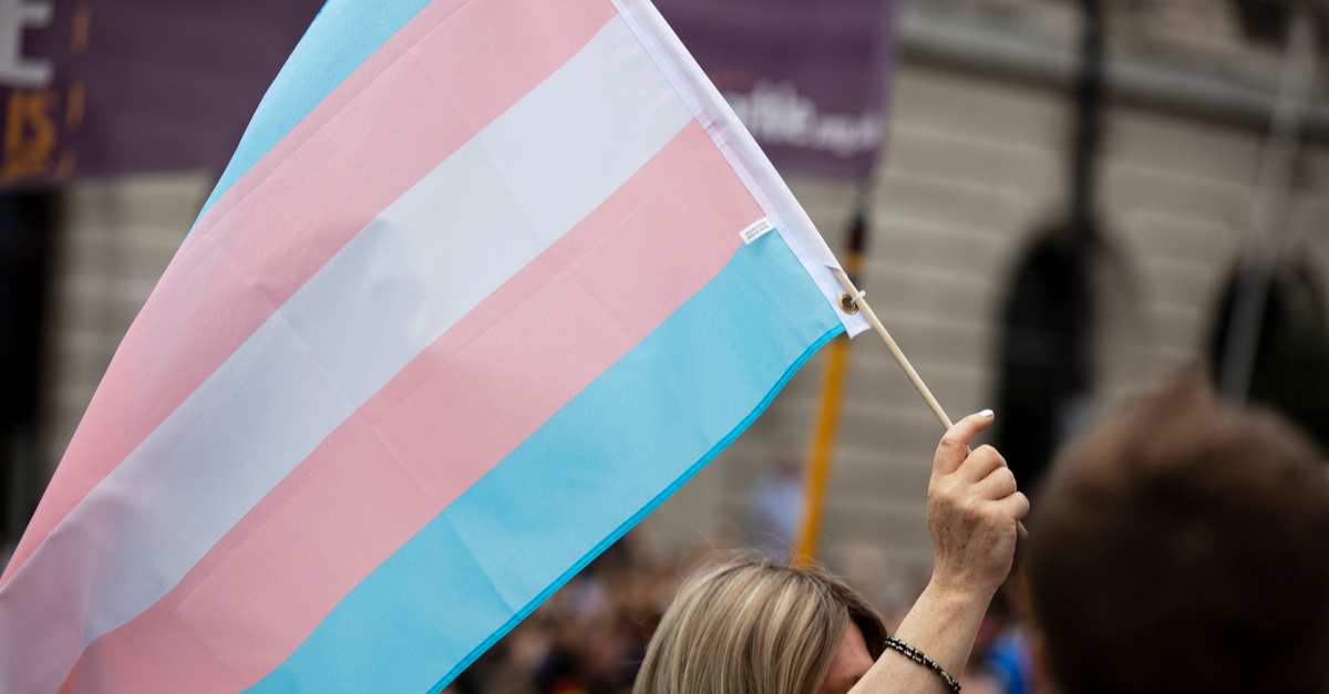 A woman holds a trans pride flag in the colors of pink, blue and white