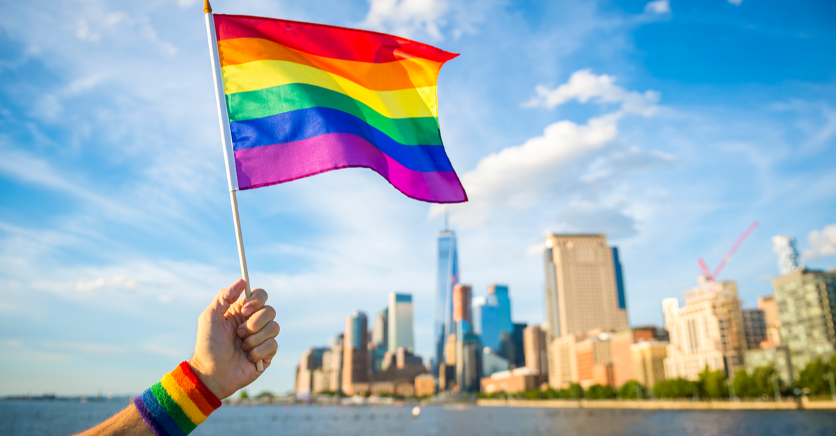 A hand is shown waving a pride flag with a cityscape in the background.