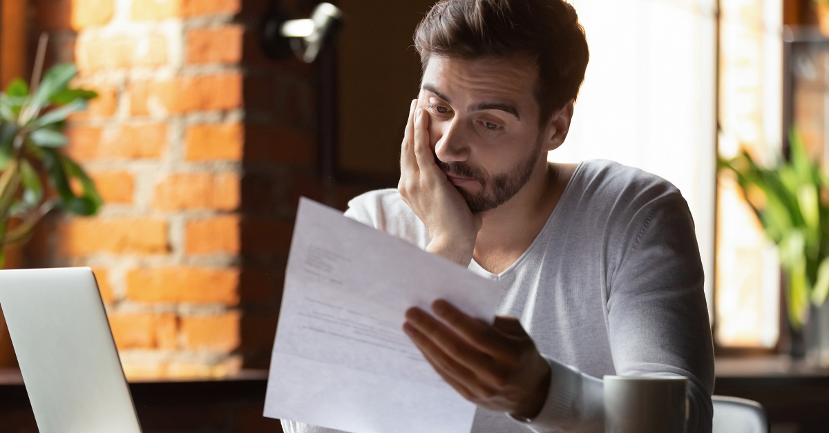 A concerned young man examines his financial statements.