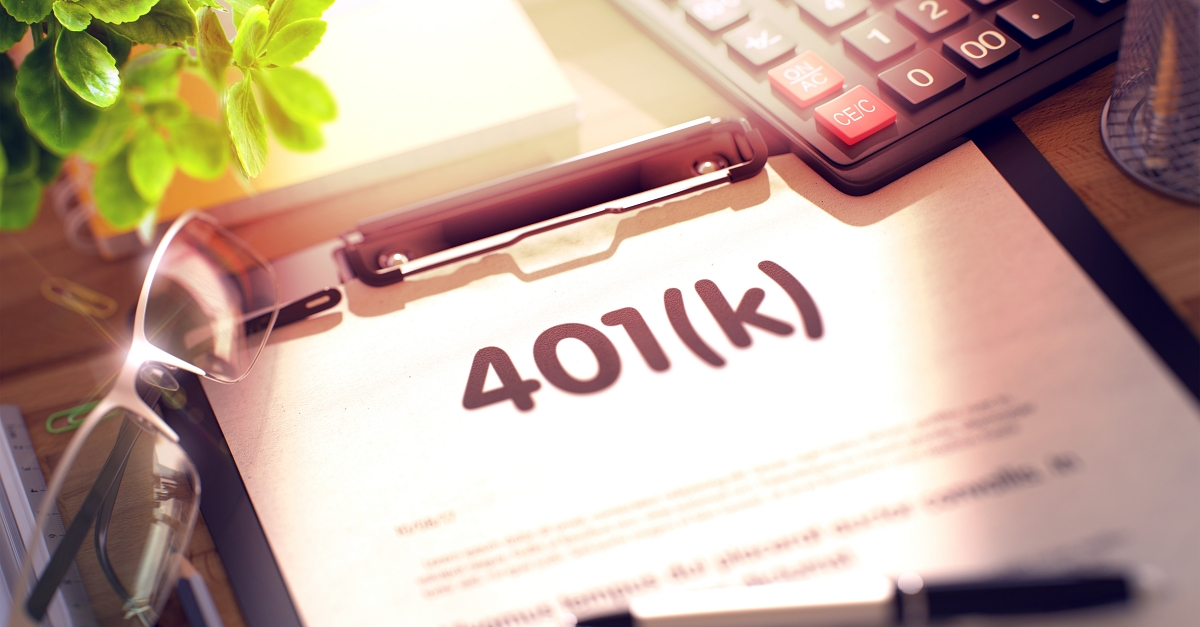 Someone prepares 401(k) documents with a calculator at their desk.