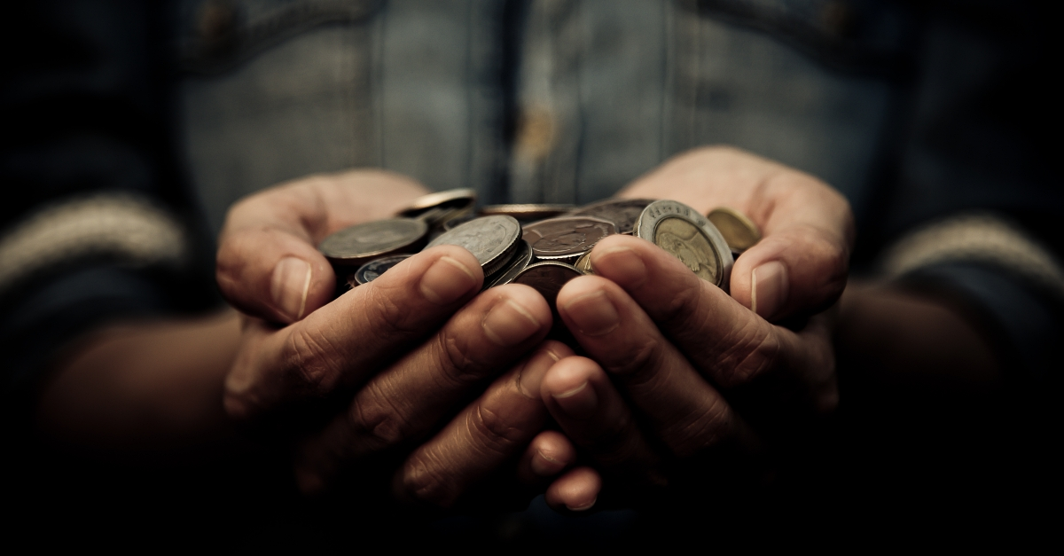 A man holds a pile of coins in his hands.