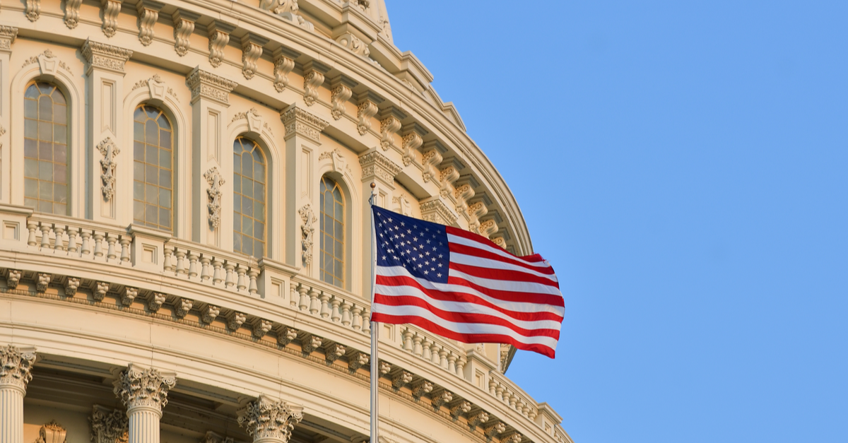 the top of the U.S. capitol building is shown with an American flag in the foreground.