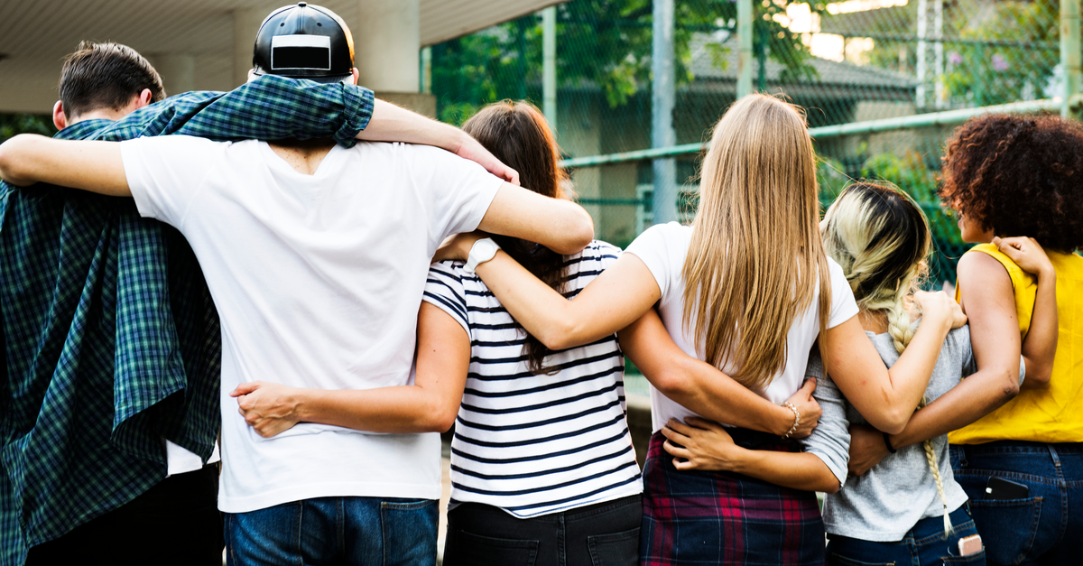 a group of teens is seen from the back with their arms interlinked