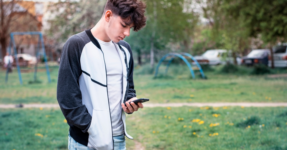 a teen boy is seen in a park using his phone to find help.
