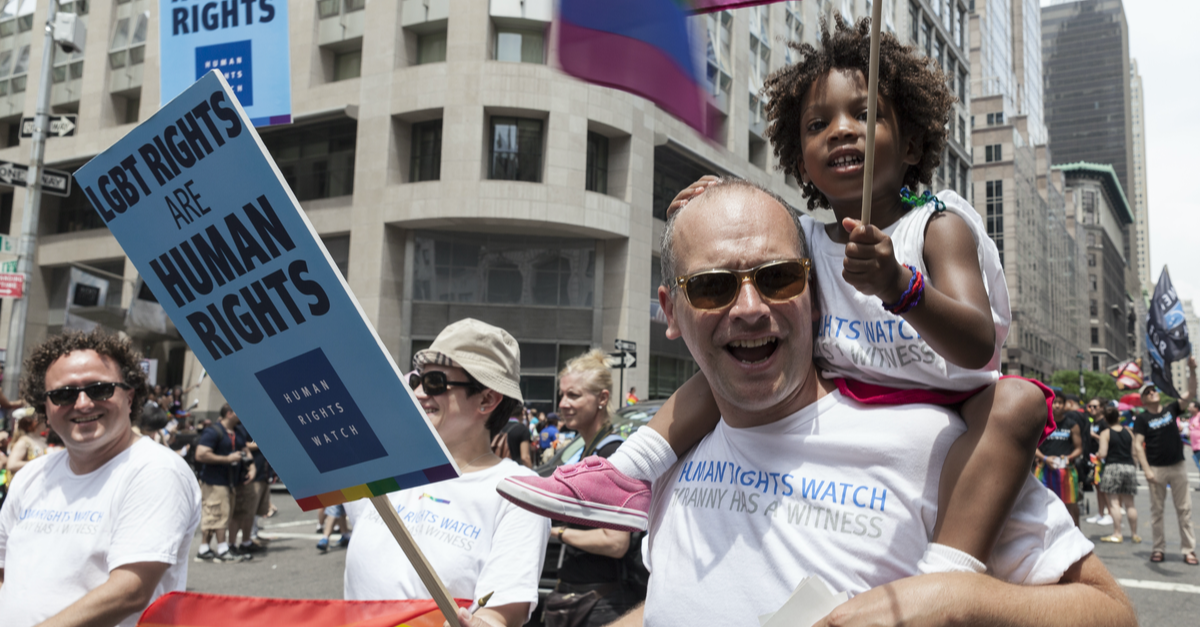 an LGBTQ+ dad marches in a pride parade with his daughter sitting on his shoulders
